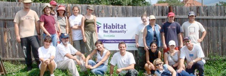 Picture of everyone standing infront of a Habitat for Humanity Banner